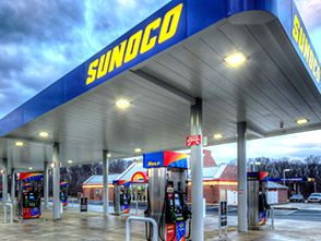 Fuel island canopy and several pumps at a Sunoco gas station