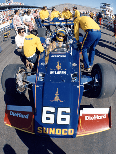 Sunoco pit crew gathered around a driver in his Sunoco-branded race car