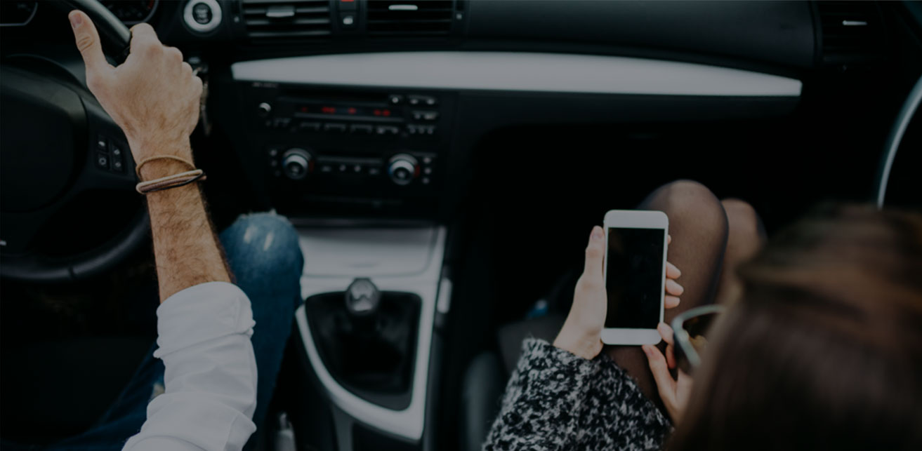 Woman holding a phone in the passenger seat of a car while man is driving