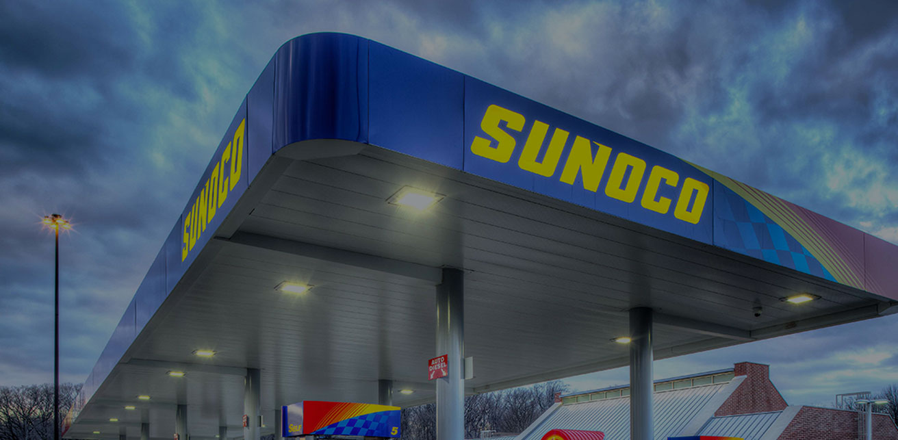Close-up shot of a fuel island canopy at a Sunoco gas station