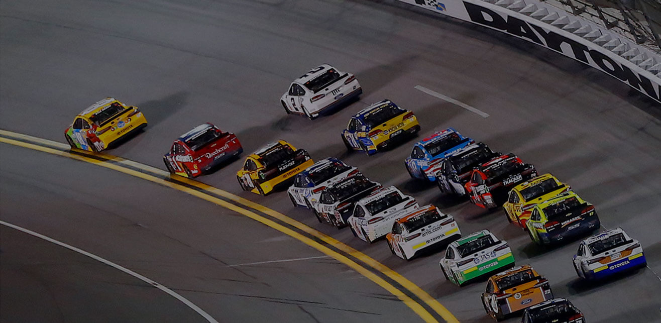 Several race cars making the turn on a race track at a major racing event