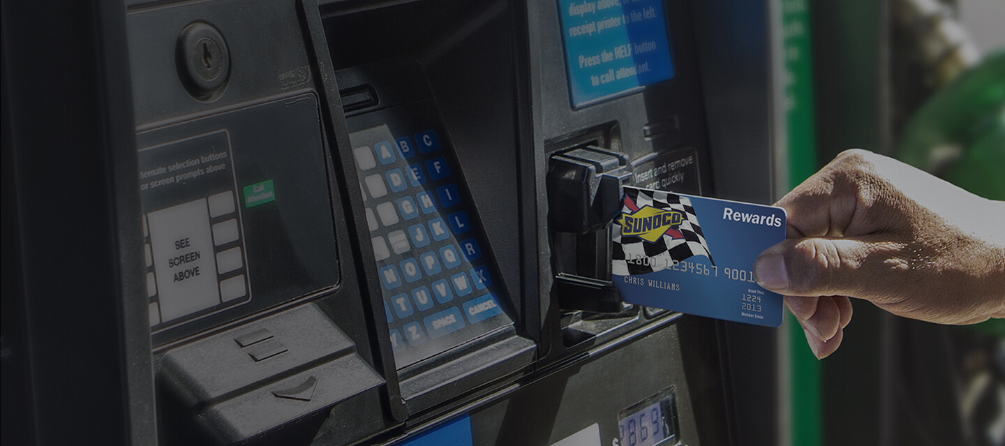 Sunoco credit card being inserted into a card reader at a gas station pump