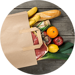Grocery bag with produce items on wooden tabletop