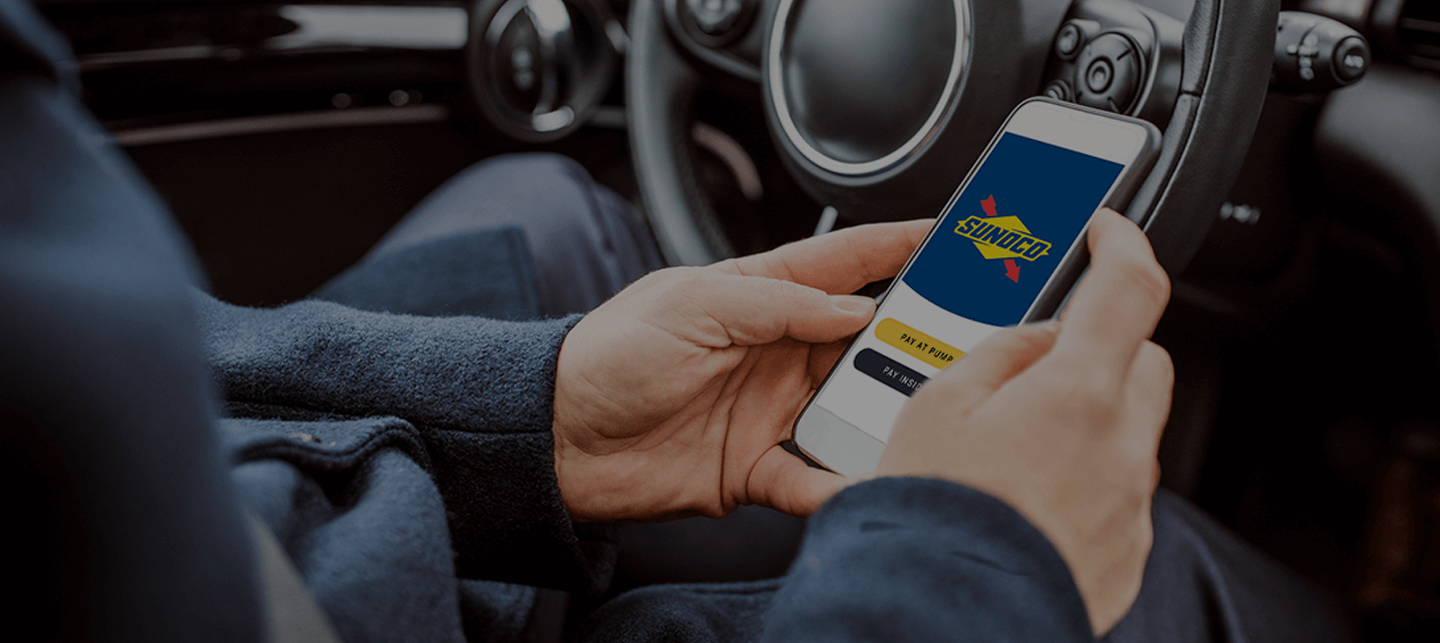 man holding phone in car while at a gas pump, looking at the Sunoco app